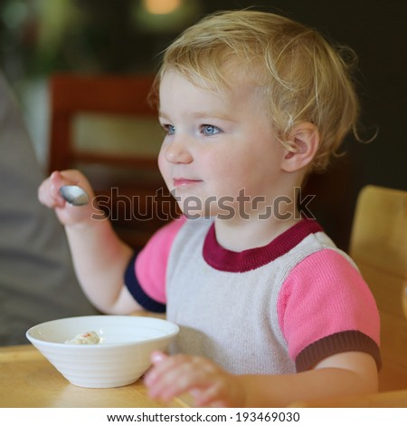 Happy little child, blonde toddler girl eating tasty ice cream from bowl in cafe - stock photo
