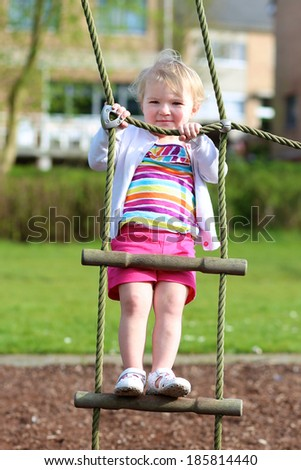 Happy little child, blonde toddler girl in colorful casual suit, having fun on the playground climbing on the rope ladder on a sunny summer day - stock photo