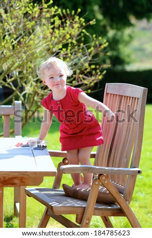 Happy little child, cute blonde toddler girl in beautiful dress playing outdoors in the garden at the backyard of the house sitting on a wooden teak chair on a sunny summer day