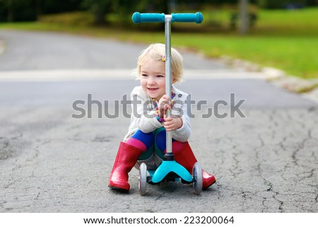 Happy little child, cute blonde toddler girl learning to ride and balance on push scooter on the street in the countryside