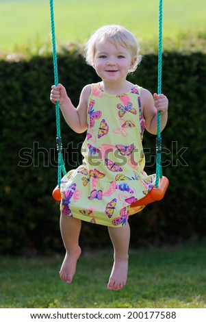 Happy little child, cute blonde toddler girl, playing outdoors in the garden at the backyard of the house swinging on playground on a sunny summer day - stock photo