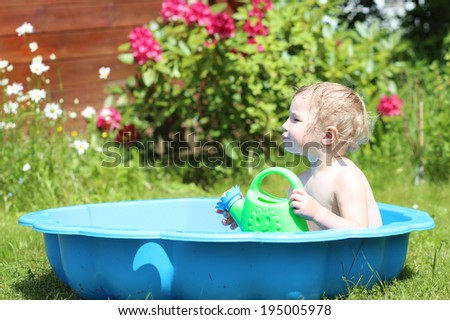 Happy little child, cute blonde toddler girl splashing in small plastic baby bath outdoors in beautiful big garden at the backyard of the house on a hot sunny summer day - stock photo
