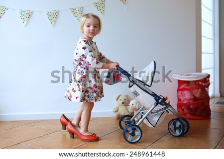 Happy little child, cute blonde toddler girl, wearing beautiful dress and red mom's shoes playing role game pushing stroller with baby doll indoors at home or kindergarten - stock photo