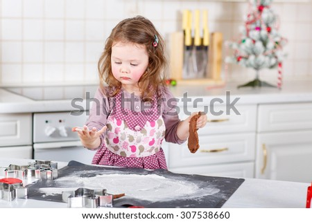 Happy little child, cute kid girl, sitting at the table in domestic kitchen making delicious sweet gingerbread xmas cookies. Kitchen decorated for Christmas - stock photo