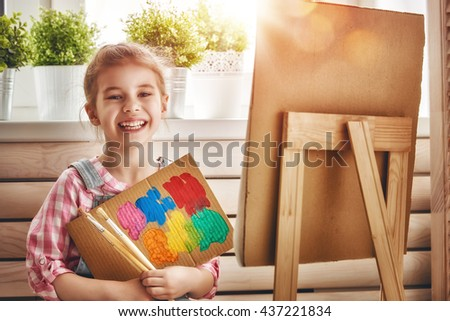 Happy little child draws paints. Sweet girl engaged in creativity. - stock photo