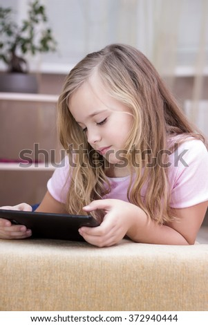 Happy little child girl enjoying modern using tablet  - stock photo
