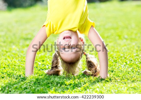 Happy little child girl have a fun standing on her head among grass - stock photo
