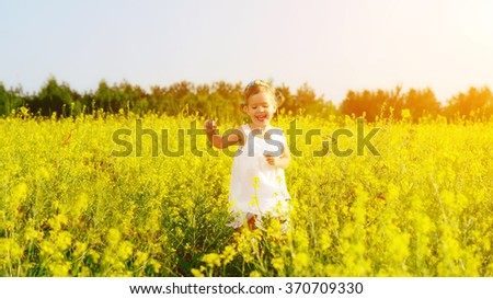 happy little child girl in a white dress running on field with a bouquet of yellow flowers,  - stock photo