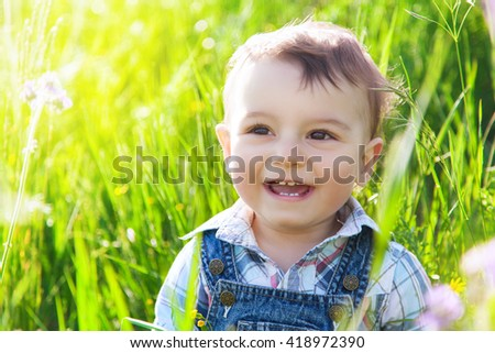 Happy little child laughing and smiling in summer green grass. - stock photo