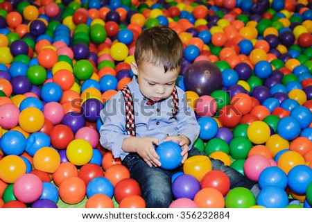 Happy little child playing at colorful plastic balls playground in dry pool. Boy having fun indoors.