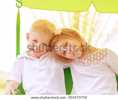 Happy little child playing outdoors in sunny day, brother with sister riding on swing, active summer holidays, happiness concept