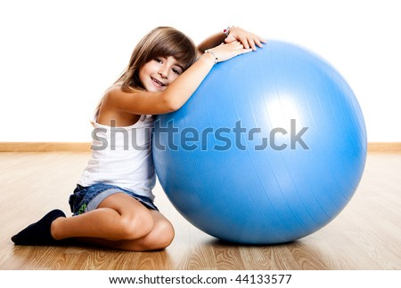 Happy little child playing with a big blue ball