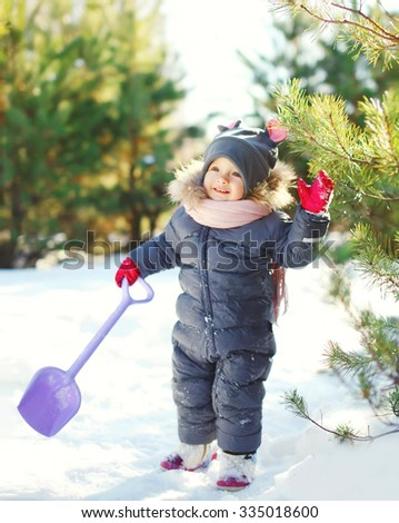 Happy little child playing with shovel toy in winter day - stock photo