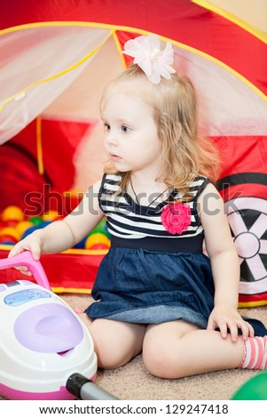 Happy little child playing with vacuum cleaner toy in domestic room - stock photo