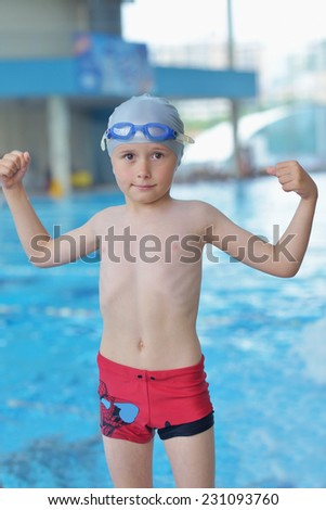 happy little child portrait on swimming school classes and recreation at indoor pool - stock photo