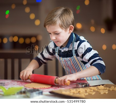 Happy little child preparing cookies for Christmas and New Year at home
