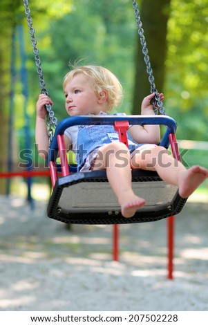 Happy little child, smiling blonde toddler girl in casual outfit having fun on a swing enjoying a warm sunny summer day on a playground in a park - stock photo