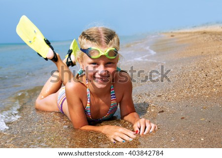 Happy little child smiling on summer beach sand with snorkel equipment looking to side at copy space after swimming with fins and mask on vacation. - stock photo