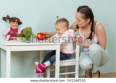 Happy little child with mother sit at the dining table in the home kitchen.