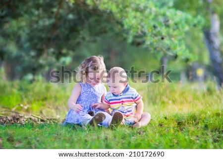 Happy little children, adorable toddler girl in a blue dress and a cute baby boy, brother and sister, playing together with pine cones sitting in a sunny forest on a warm summer day
