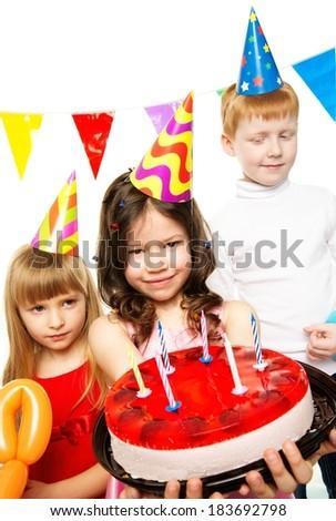 Happy little children celebrating birthday with cake - stock photo
