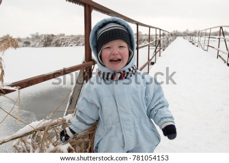 Happy little children in colorful clothes play with snow and icicles. Scenic area with a bridge on the river. Winter vacation concept, Christmas, New Year