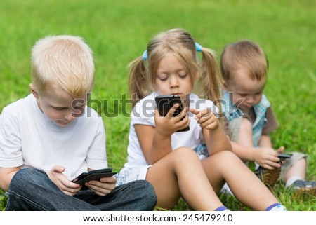 Happy little children playing in smartphones in the park. Brothers and sister. - stock photo