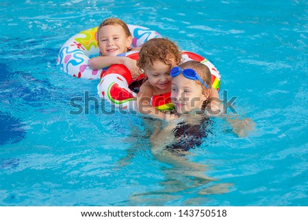 happy little children playing in the swimming pool