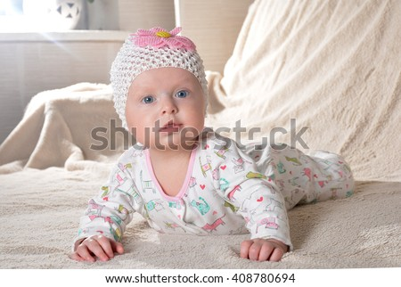 happy little cute baby girl in a dress and with flower smiling at home - stock photo