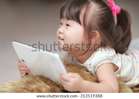 Happy little cute girl with tablet pc lying on the doll - stock photo