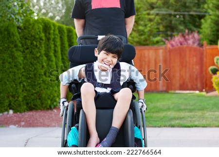 Happy little disabled boy wheeling around outdoors in wheelchair - stock photo