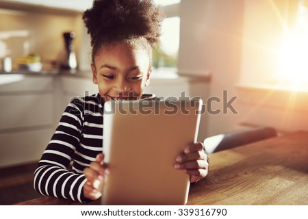 Happy little ethnic black girl sitting at home in the kitchen reading on a tablet computer grinning with pleasure, bright sun glow behind - stock photo