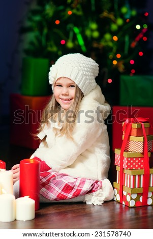 happy little fashion girl in white knitted clothes with Christmas light and eve and candy - stock photo