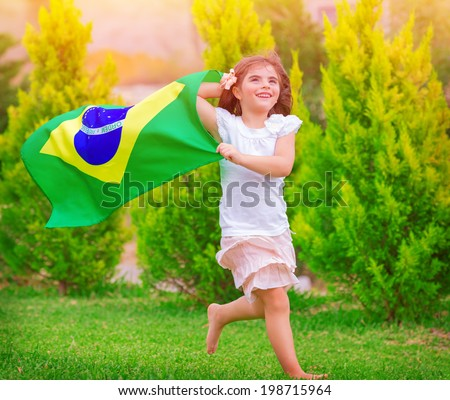 Happy little football fan, cute little girl running on the park with national Brazil flag waving on the wind, sportive childhood, football championship concept - stock photo