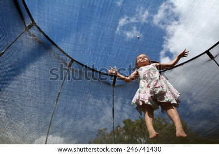 Happy little girl (age 04) jumps on a trampoline. - stock photo
