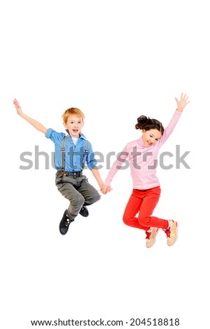 Happy little girl and boy jumping for joy together. Children. Isolated over white. - stock photo