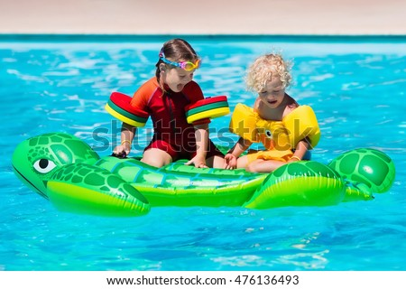 Happy little girl and boy playing in outdoor swimming pool sitting on inflatable toy turtle in a tropical resort during family summer vacation. Kids learning to swim.