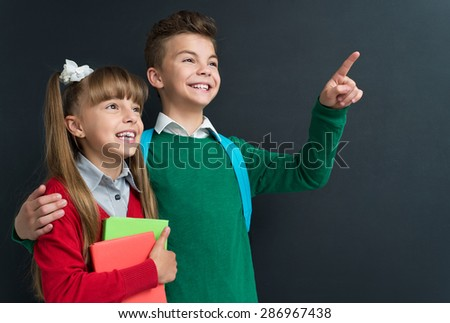 Happy little girl and boy pointing at something at the black chalkboard in classroom. - stock photo