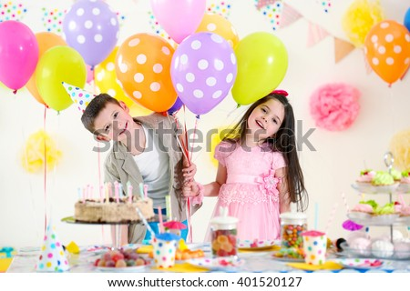 Happy little girl and boy with balloons having fun at birthday party