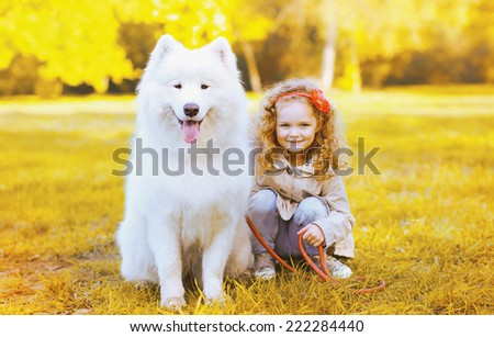 Happy little girl and dog having fun in sunny autumn day