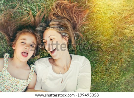 happy little girl and her mother having fun outdoors on the green grass in sunny summer day  - stock photo