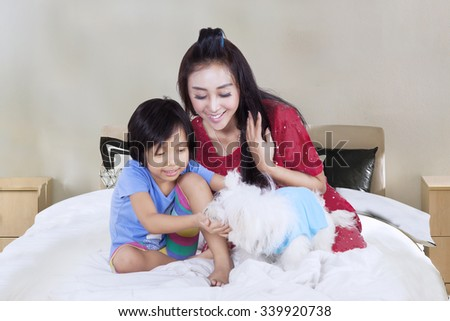Happy little girl and her mother sitting on the bed while playing with their puppy