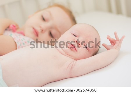 Happy little girl and her newborn brother - stock photo