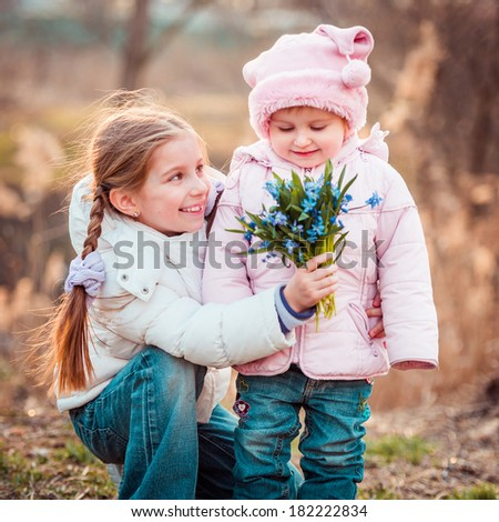 happy little girl and her sister holding a bouquet of snowdrops - stock photo