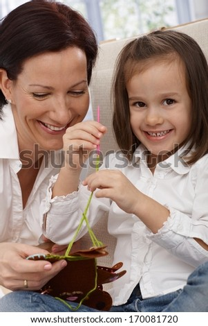 Happy little girl and mother doing needlework, having fun. - stock photo