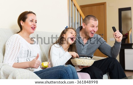 Happy little girl and parent sitting with popcorn in front of TV. Focus on woman - stock photo