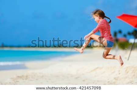 Happy little girl at beach having a lot of fun on summer vacation - stock photo