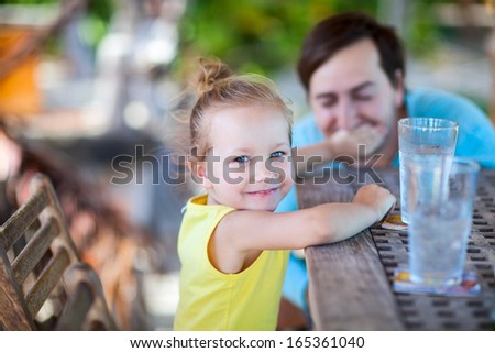 Happy little girl at outdoor restaurant or cafe with her father - stock photo