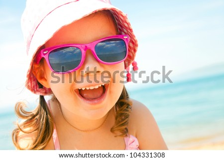 happy little girl at the seaside in the summer