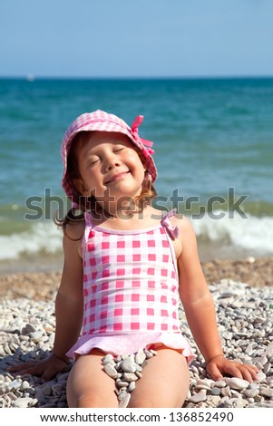 happy little girl at the seaside in the summer - stock photo